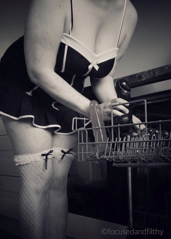 Black and white photograph of a woman wearing a skimpy dress and white fishnet stockings loading a dishwasher with dildos