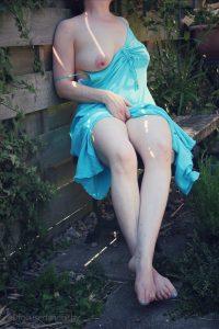 Colour photograph of woman wearing a turqouise summer dress sat on a bench outside with one breast hanging out of her dress and one hand between her legs