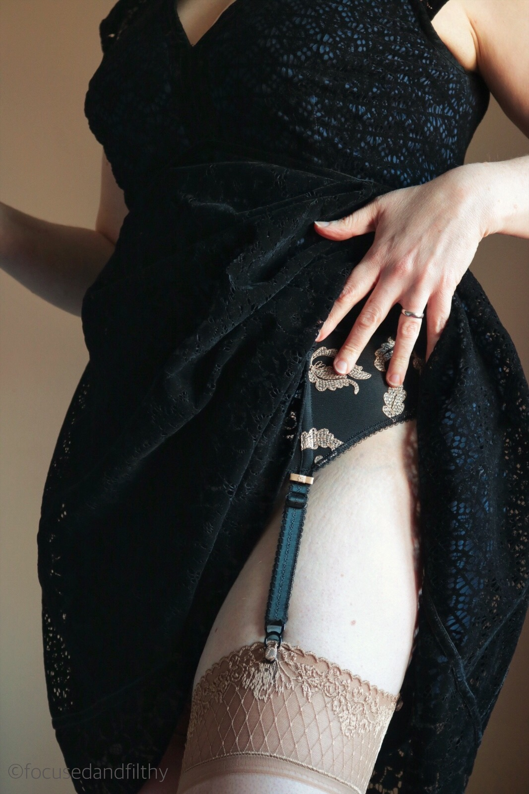Colour image of a short black dress being lifted to show a stocking top and black suspender belt