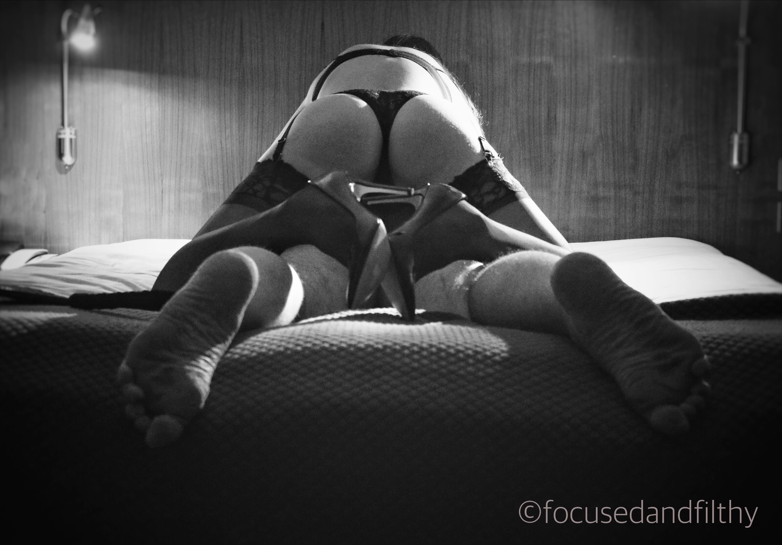 Black and white image of a man laying naked faces down on the bed and a woman sat straddling him from behind. Focusing on her high heels and stockings and his arse.