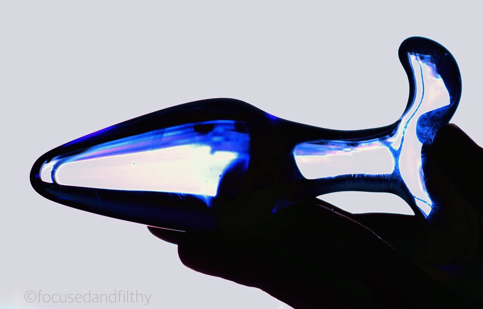 Colour photograph of a blue glass butt plug held flat in a hand like a torpedo