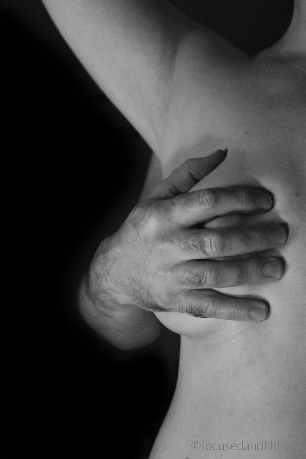 Black and white photograph of half a female naked torso from neck to waist, with a male hand grasping her over her right breast. Background is black.