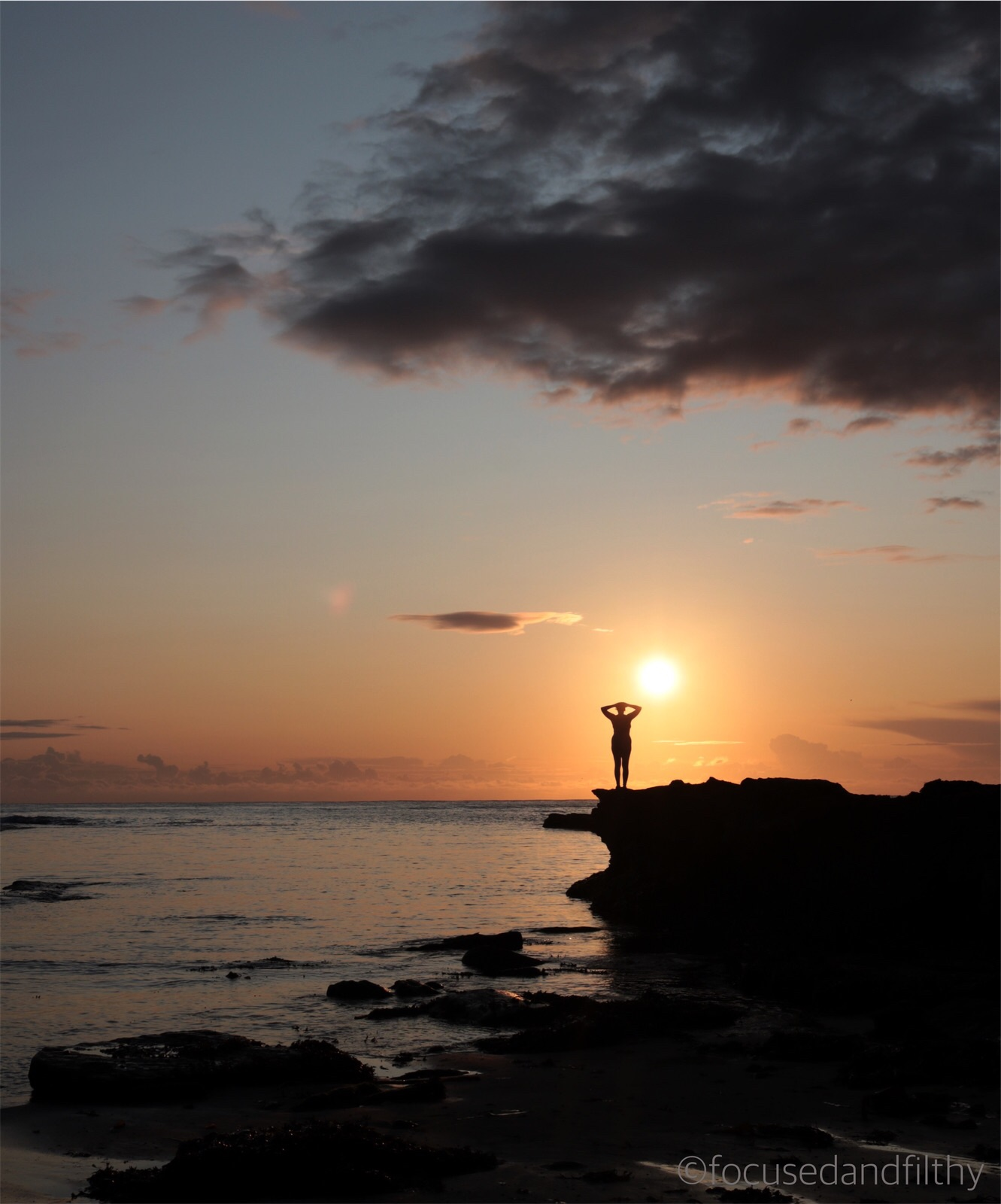 Colour photograph of a sunrise over the sea and some rocks and silhouetted on the rocks is a naked woman stood with her arms up.