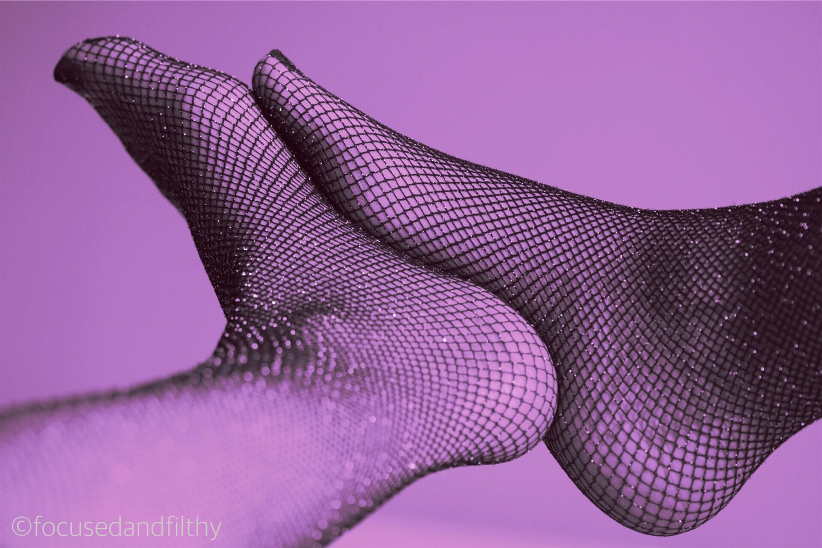 Photograph of two feet pressed together in sparkly fishnet stockings. The editing has the whole image looking quite purple
