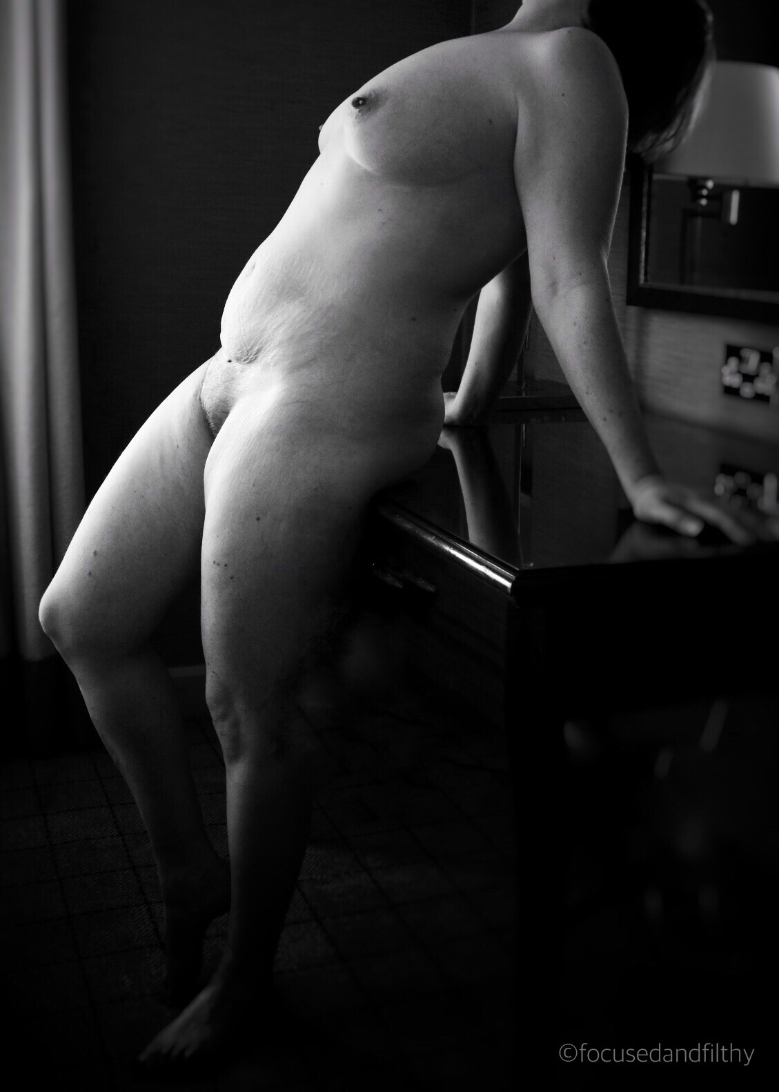 Black and white photograph of a naked woman stood up and leaning back against a wooden desk. Light across her front and dark behind her