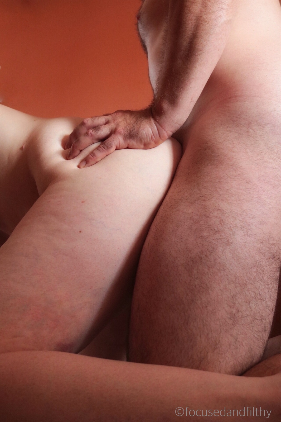 Colour photograph of a naked Male and female couple from the side during doggy style sex. Focusing on his hand gripping onto the soft flesh of her buttock.