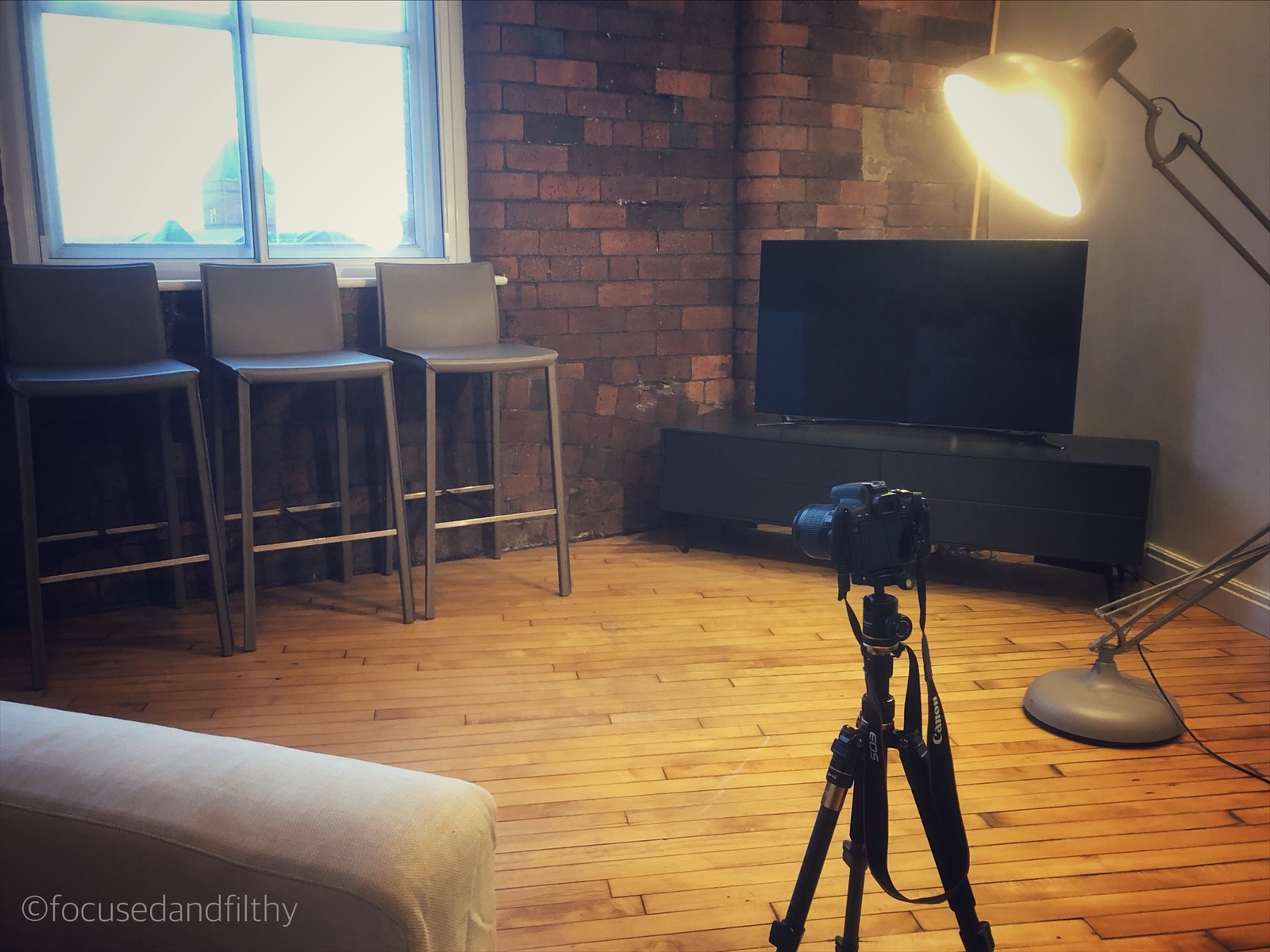 Colour photograph showing a camera on a tripod in a a large room with wooden floors and brick walls and three empty stools facing it