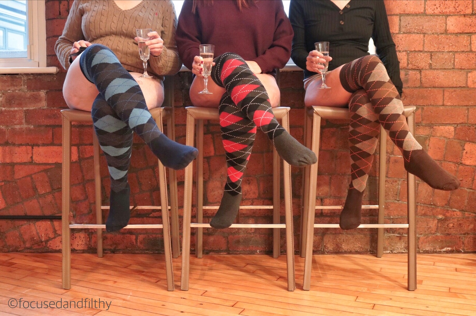 Colour photograph of three women sat on tall stools wearing jumpers and matching long argyle socks in different colours blue red and brown, the image only goes up to neck height and each woman is holding a glass of wine. The background is industrial red brick and wooden floor boards