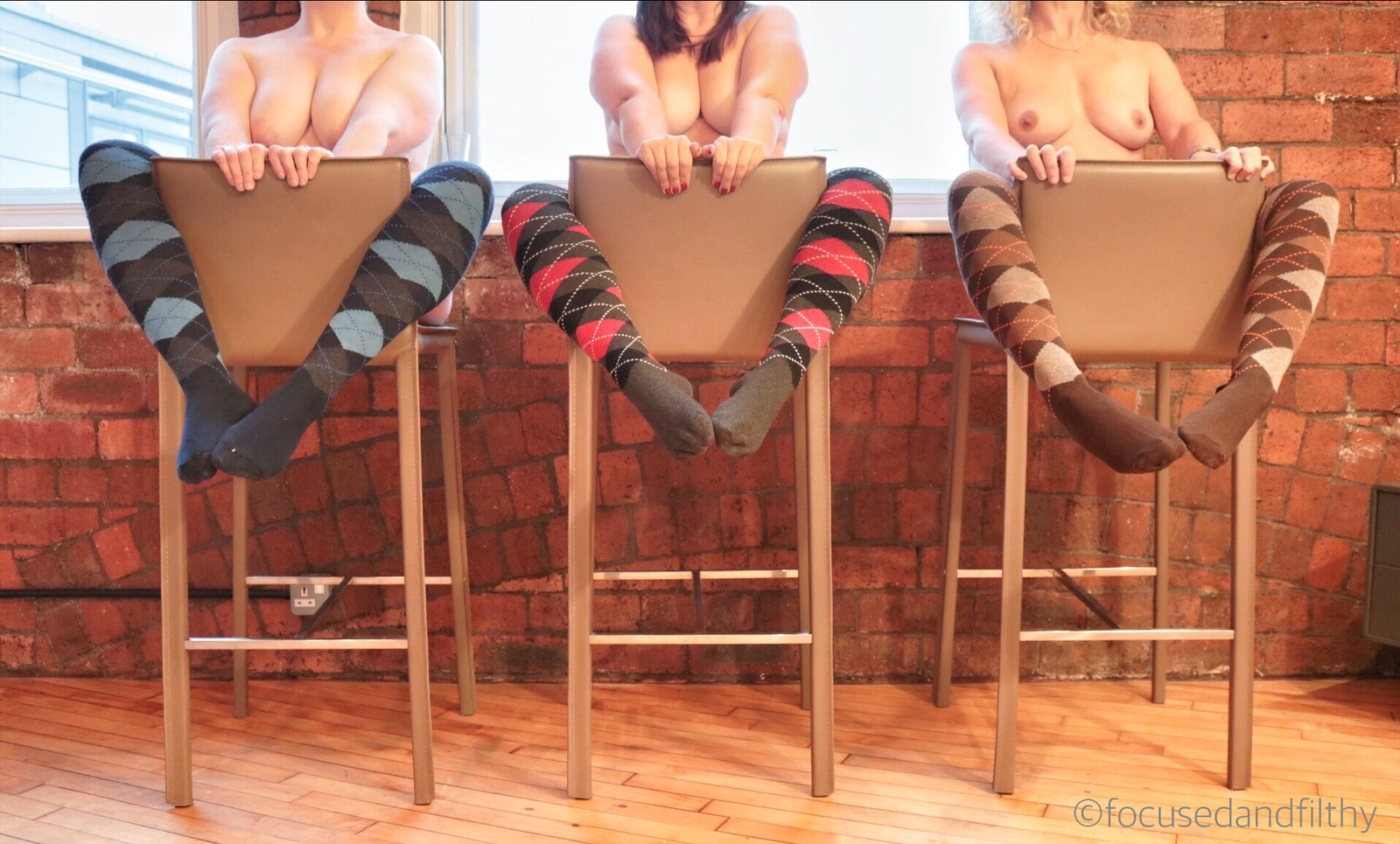 Colour photograph of three women sitting on three backward bar stools against a red brick wall. They are naked apart from long coloured argyle socks and their are leaning back with their feet up and toes touching in the middle knees opened.