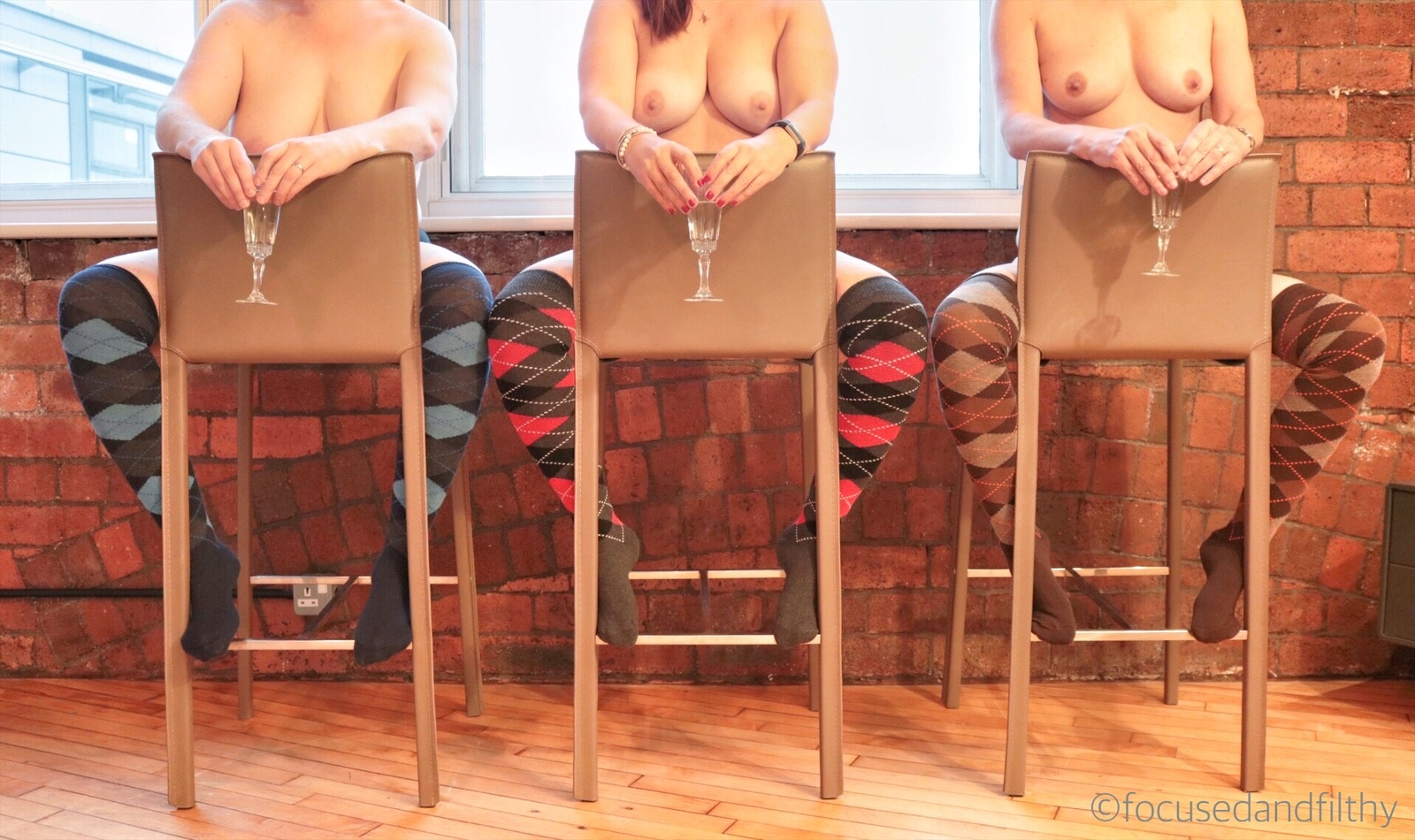 Colour photograph of three women sat on three backward bar stools against a red brick wall. They women are naked apart from long colourful argyle socks and they are each holding a champagne flute in the middle.