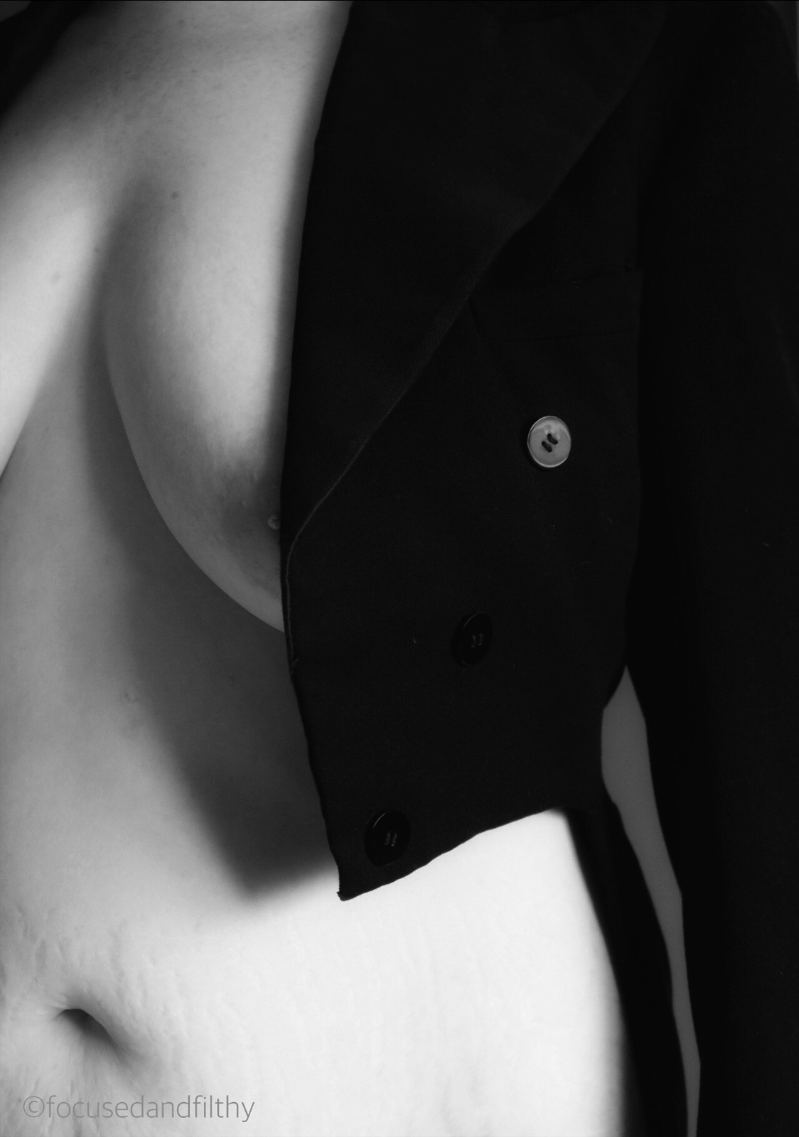 Black and white photograph of a woman from neck to waist showing her wearing just a tailcoat that just covers her left breast and shows the curve of her waist