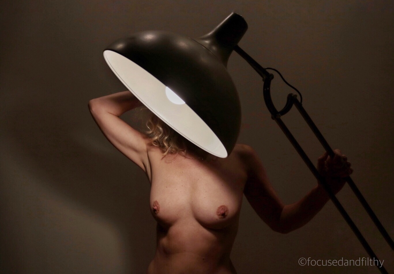 Colour photograph of a naked woman stood behind a gentle angle-poised lamp. The lamp is covering her face and head but the light is on her body showing her naked breasts and she is holding one arm up to her head and one holding the arm of the large lamp.