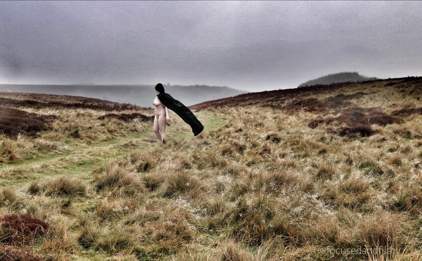 Colour photograph of a naked woman in a dark green cloak stood on a desolate Yorkshire Moor with the cape blowing behind her in the wind. Looking very windswept.