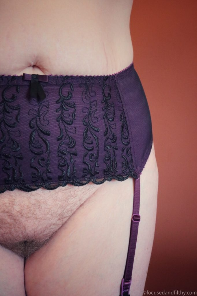 Close up colour photograph of the left side of my stomach area  I'm wearing only a purple lacing suspender belt with black lace details over the top and no knickers