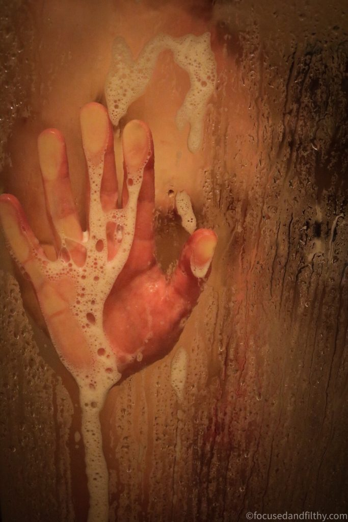 Colour photograph of a soapy hand seen pressed against a steamed up abd wet shower screen  with the hint of a woman behind it