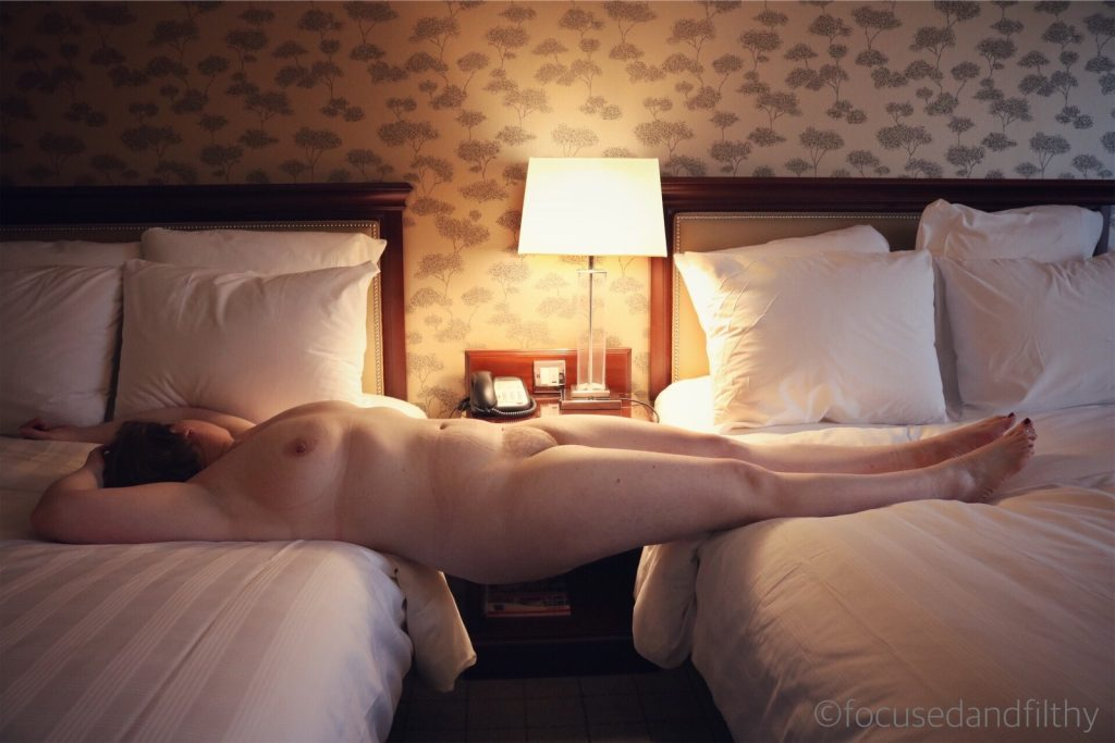 Colour photograph of a naked woman lying flat between two double beds