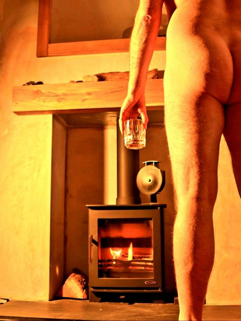 Colour photograph in warm organs tones of a naked lower half of a man seen from behind  stood in front of a log burner fire holding a glass of whiskey