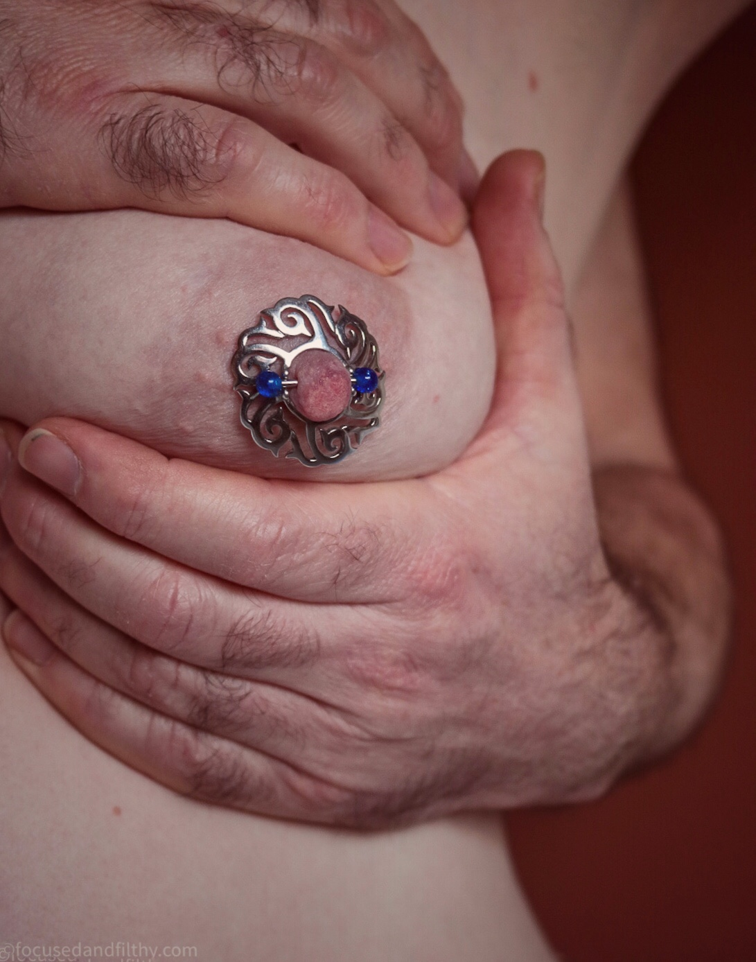 Colour photograph of a naked left female breast held firmly with two Male hands and wearing a large silver Celtic nipple shield and a blue nipple bar.