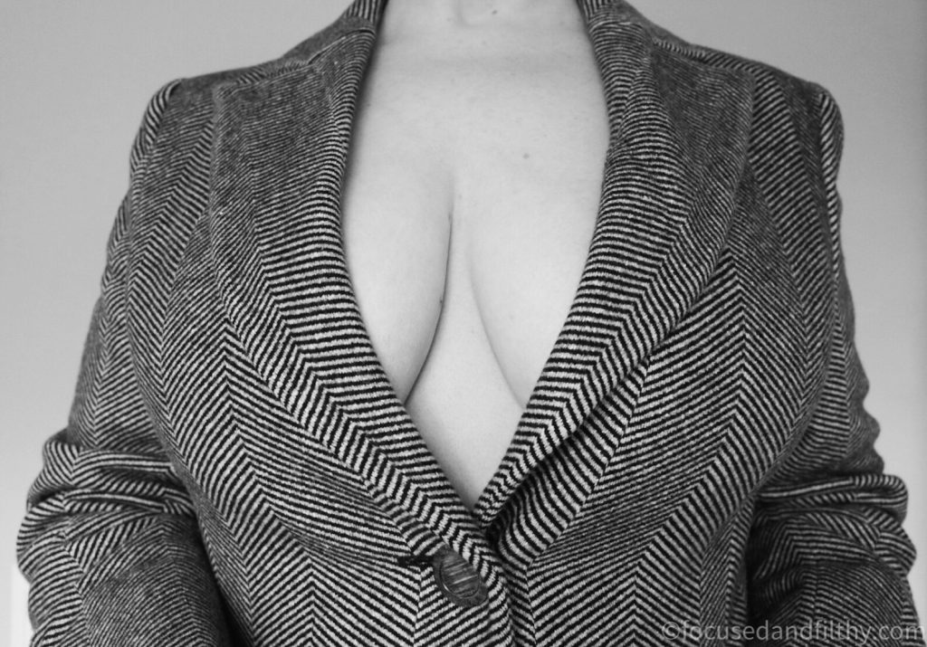 Black and white photograph of a female torso wearing a wool coat and nothing underneath   Cleavage seen