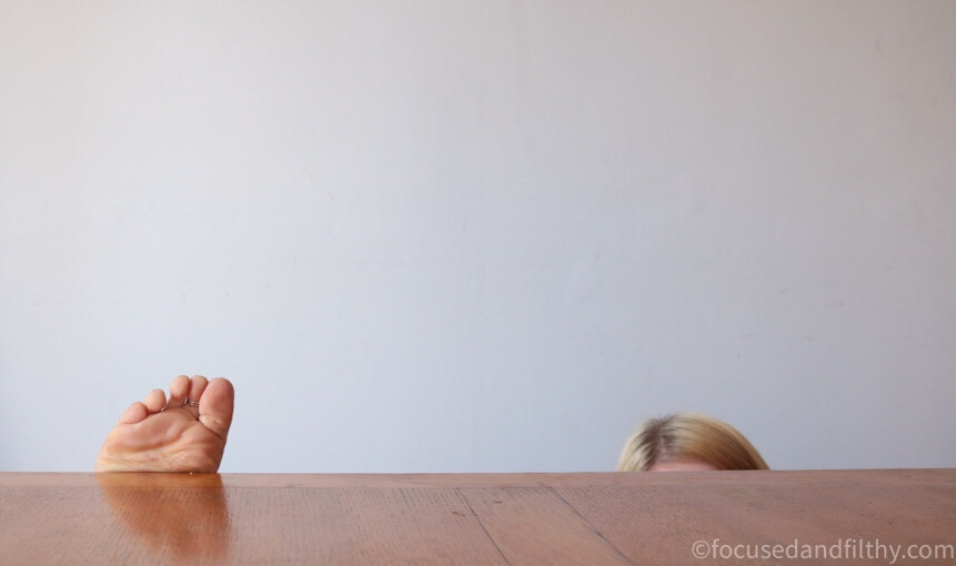 Colour photograph of a clear table top with just peaking over the top one set of toes and the top of my head