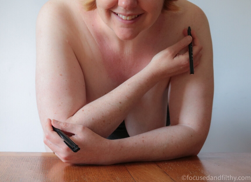 Colour photograph of my naked leaning over a table with pens in my hands one near by elbow and one pointing to my shoulder and smiling