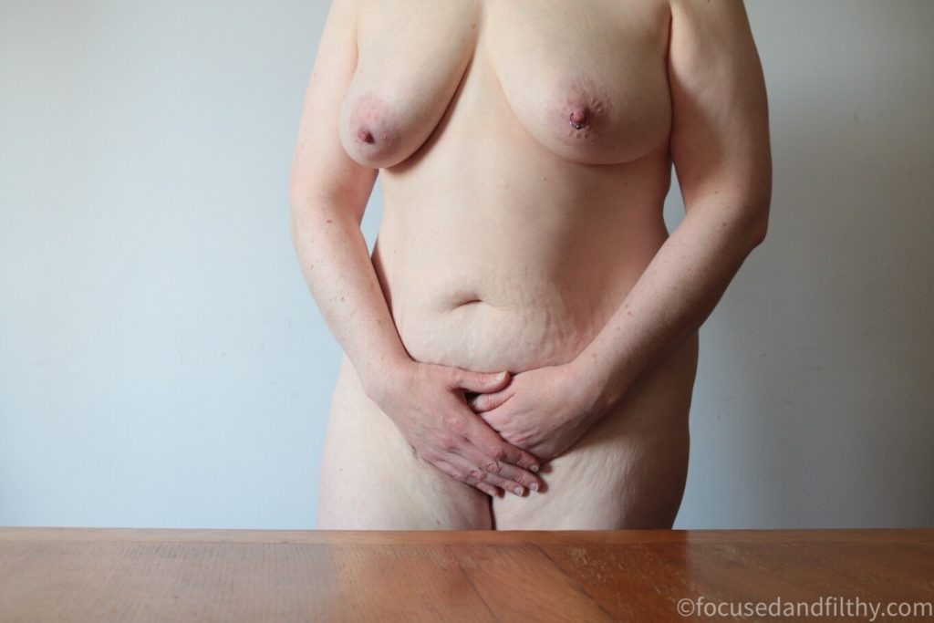 Colour photograph of a naked woman standing behind a wooden table showing her from thighs to neck with her hands over her bits but showing her naked  breasts