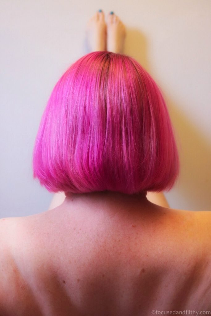 Close up colour photograph of the back of a pink bob hair cut   The pink is bright fuchsia   You can see naked legs up the wall behind them