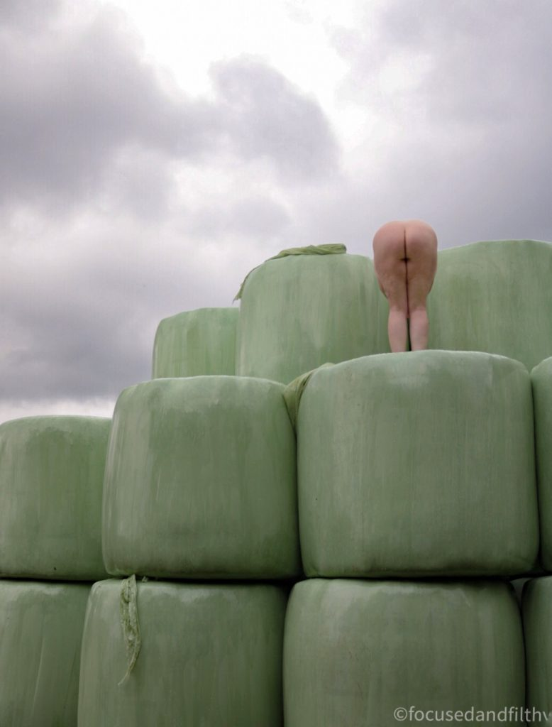 Colour photograph of some green plastic wrapped sillage bales with a naked woman stood on top  bending over showing her naked bottom