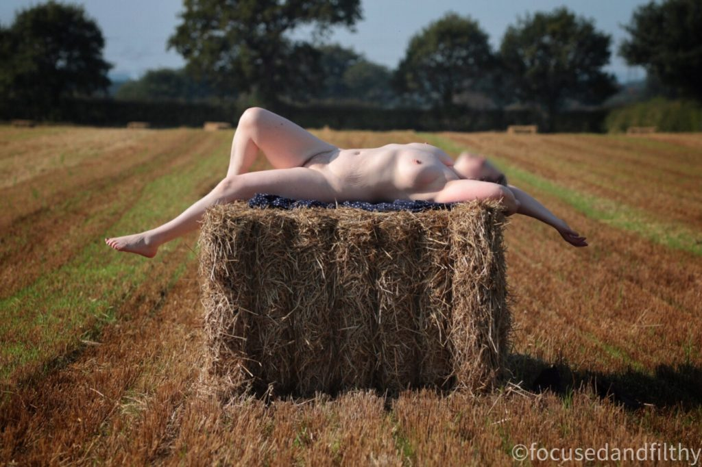Colour photograph of a pale naked woman lying on top on a rectangular hay bale