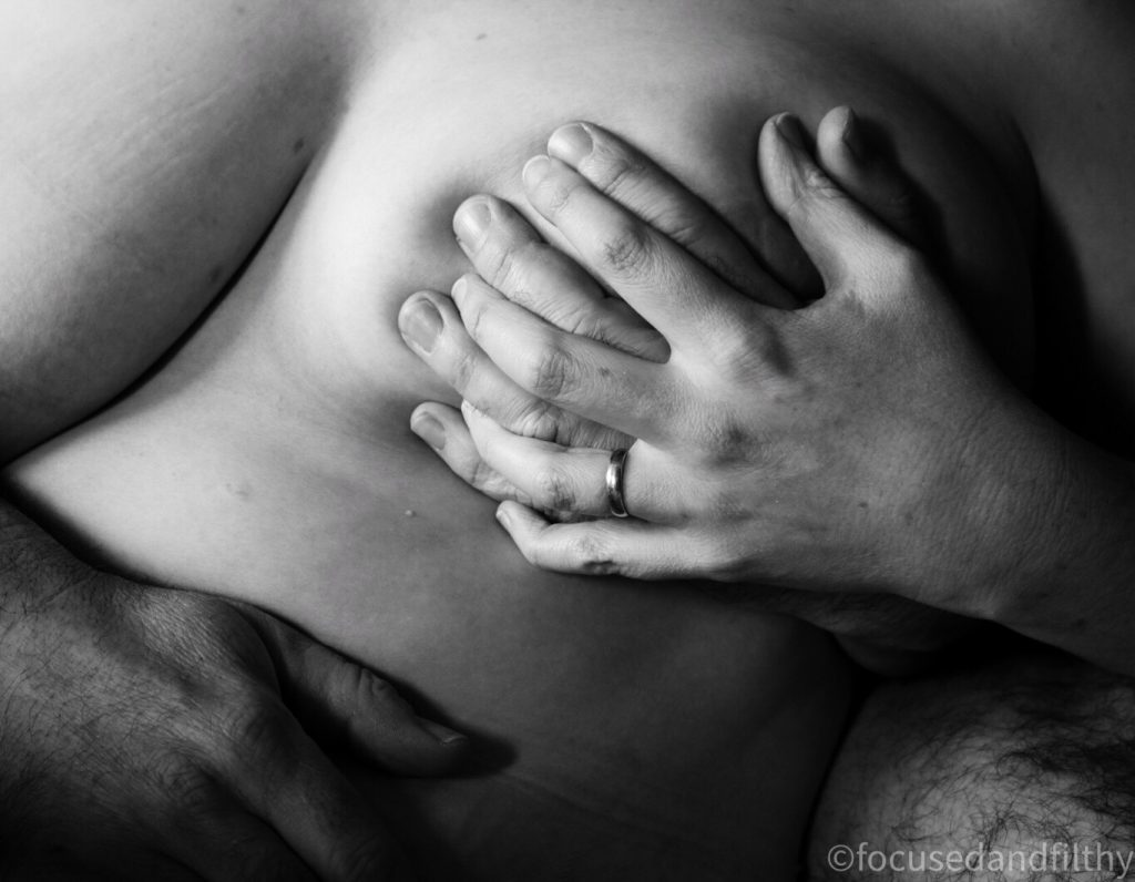 Black and white photograph of a blokes hand grasped over a naked breast with a woman's hand held over it  holding it together
