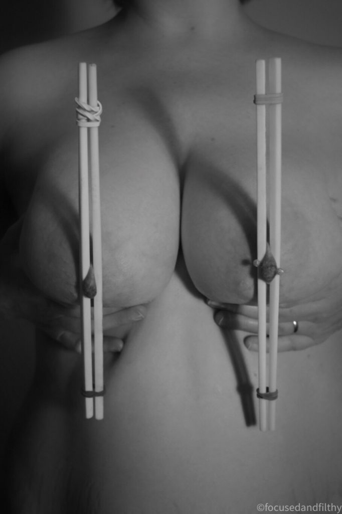 Black and white photograph of a naked woman's torso with chopsticks made nipple clamps running vertical over both nipples and the breasts being held forward for the camera
