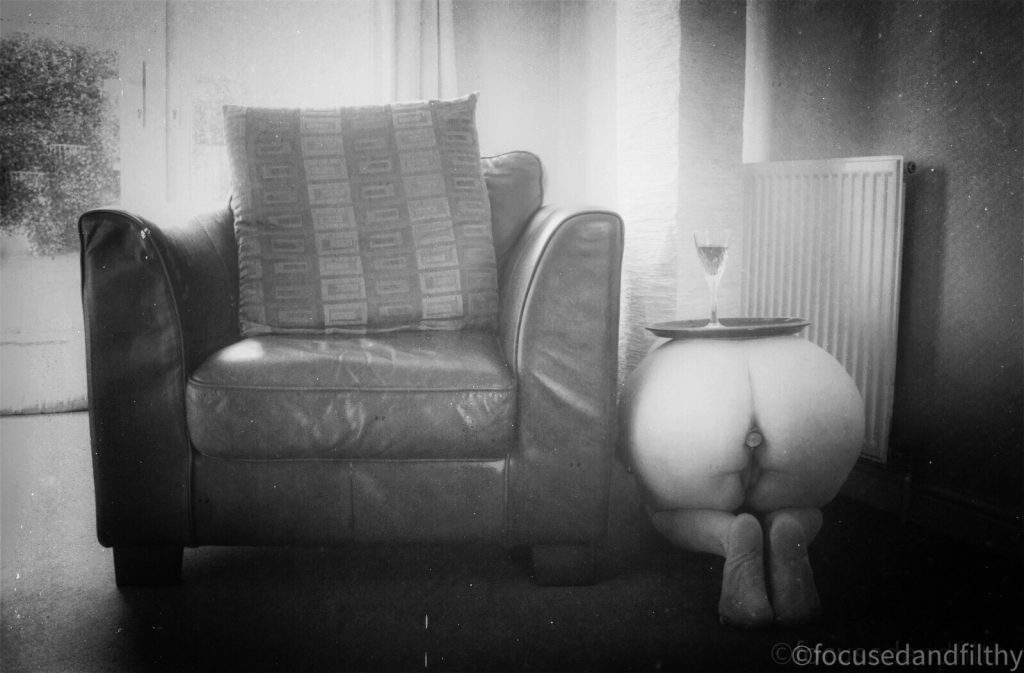 Black and white photograph of a single sofa seat and next to it is a naked woman with a tray on top and a wine glass acting as a side table  only her bottom is on display