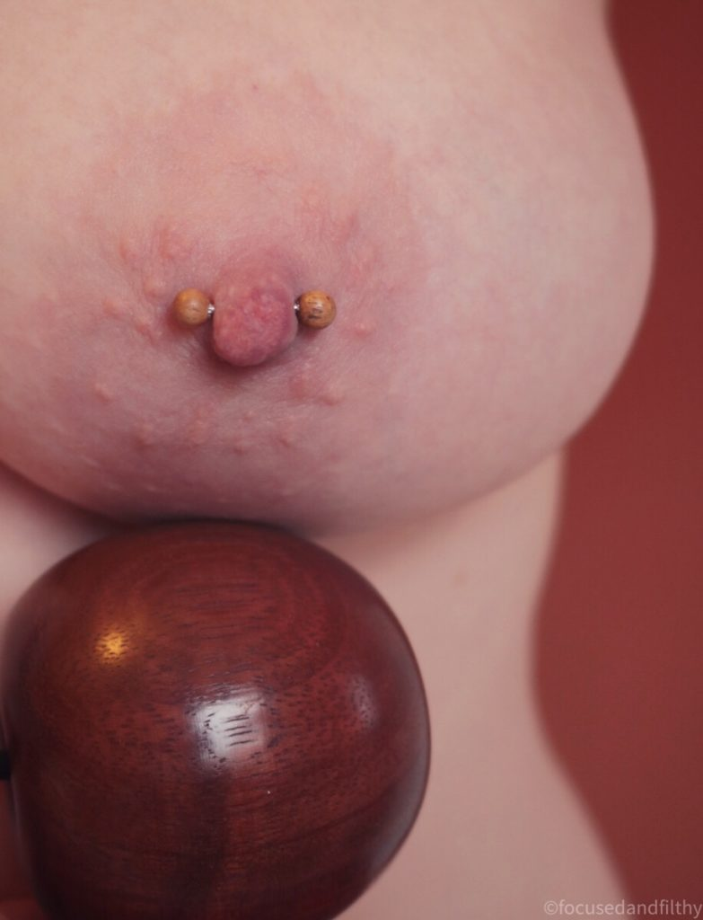 Colour photograph of my left naked breast with a nipple bar in with small teal wooden balls on the end there is also a darker wooden ball just under my breast reflecting the curve of the breast and my side