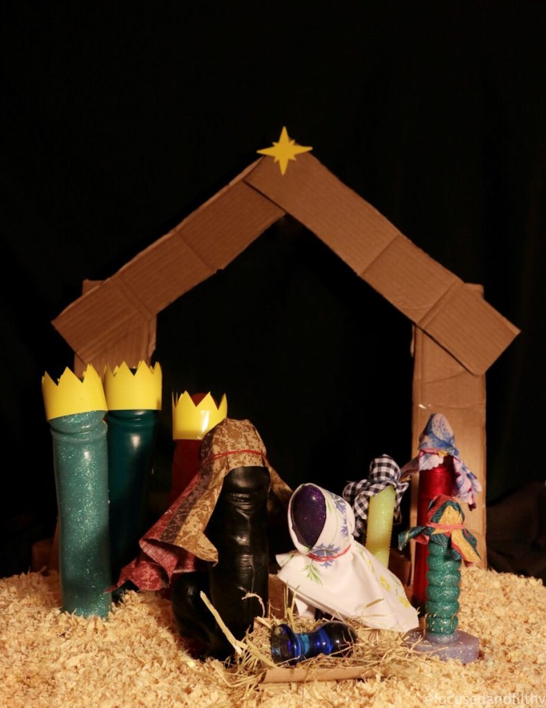 Colour photograph of a dildo nativity scene including three tall dildos wearing crowns, three smaller disposable wearing tea towel like head dressers as shepherds, Joseph is a large black dildo with balls and Mary is a purple sparkly dildo with a white shawl , Jesus in a manger is a small blue glass butt plug it is staged on a dark night in a cardboard stable with a bright star above and sawdust all around