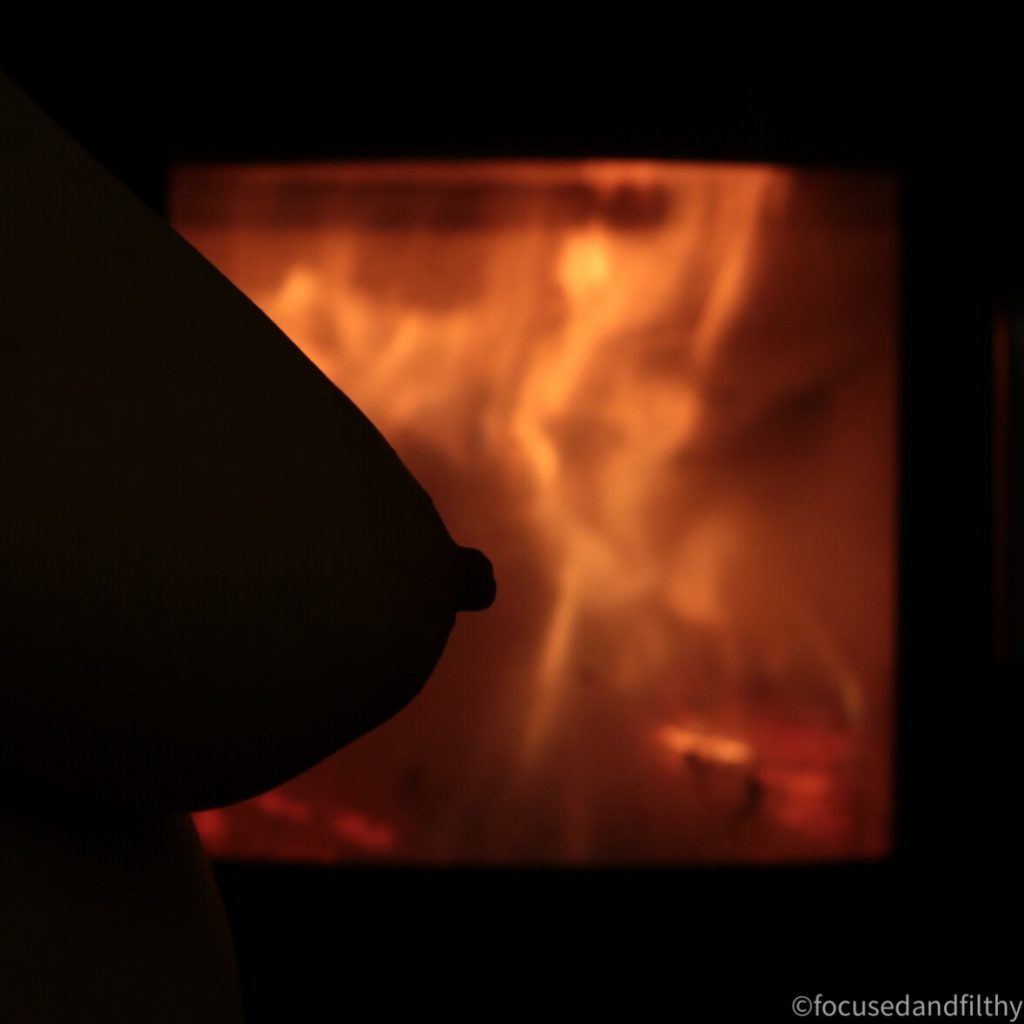 Colour photograph of a naked breast silhouetted against a orange fire (stove window)