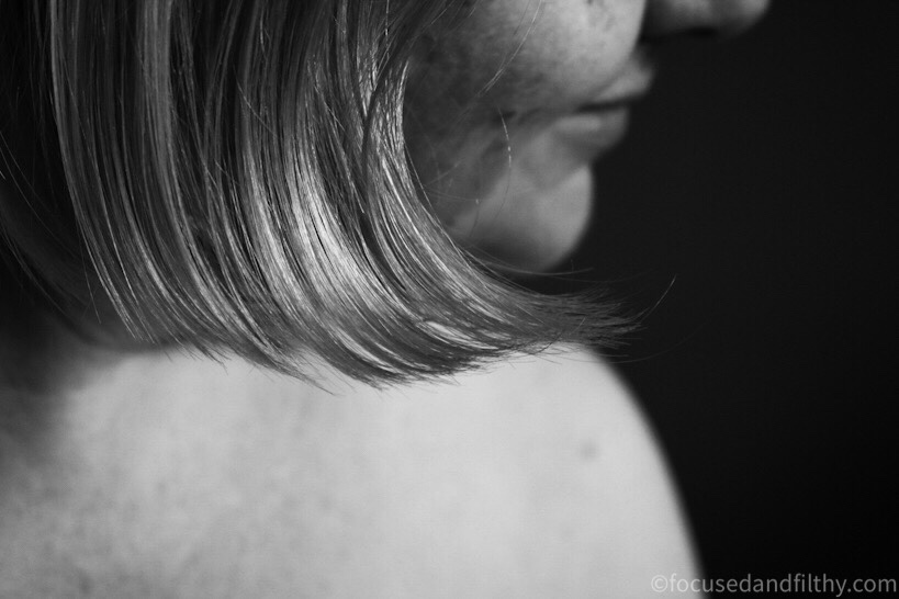Close up black and white photo of the edge of my pale bobbed hair and my blurred face in the background with a hint of a smile