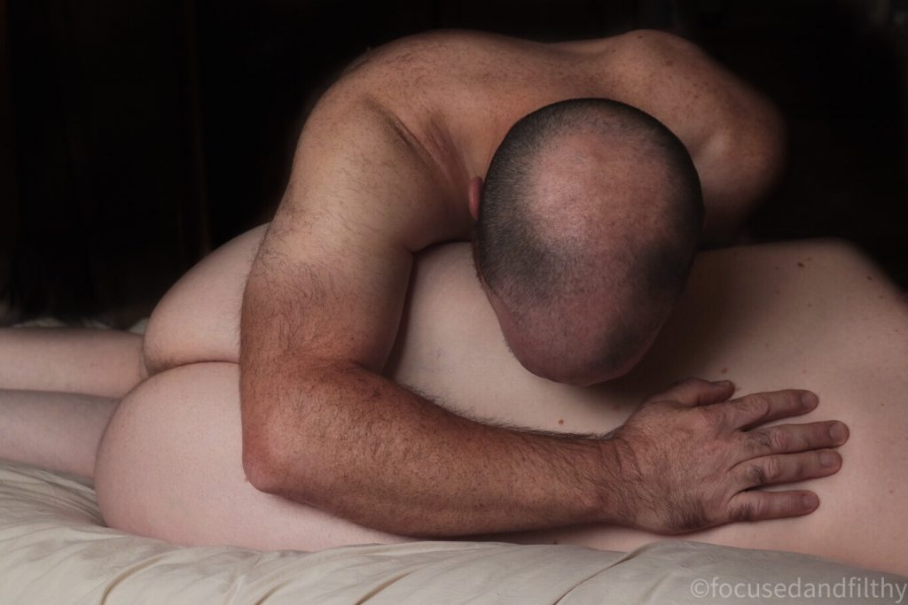 Colour photograph showing a naked woman lying on her side with her back to the camera  over her body is a male with his head resting into her waist and a protective hand on her back  she has very pale skin  he has tanned brown skin