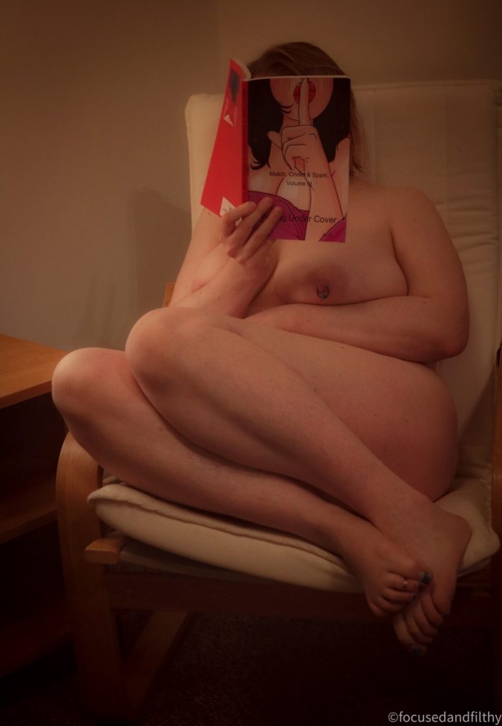 Colour photograph of a naked woman curled up on a  chair reading a book which is obscuring her face