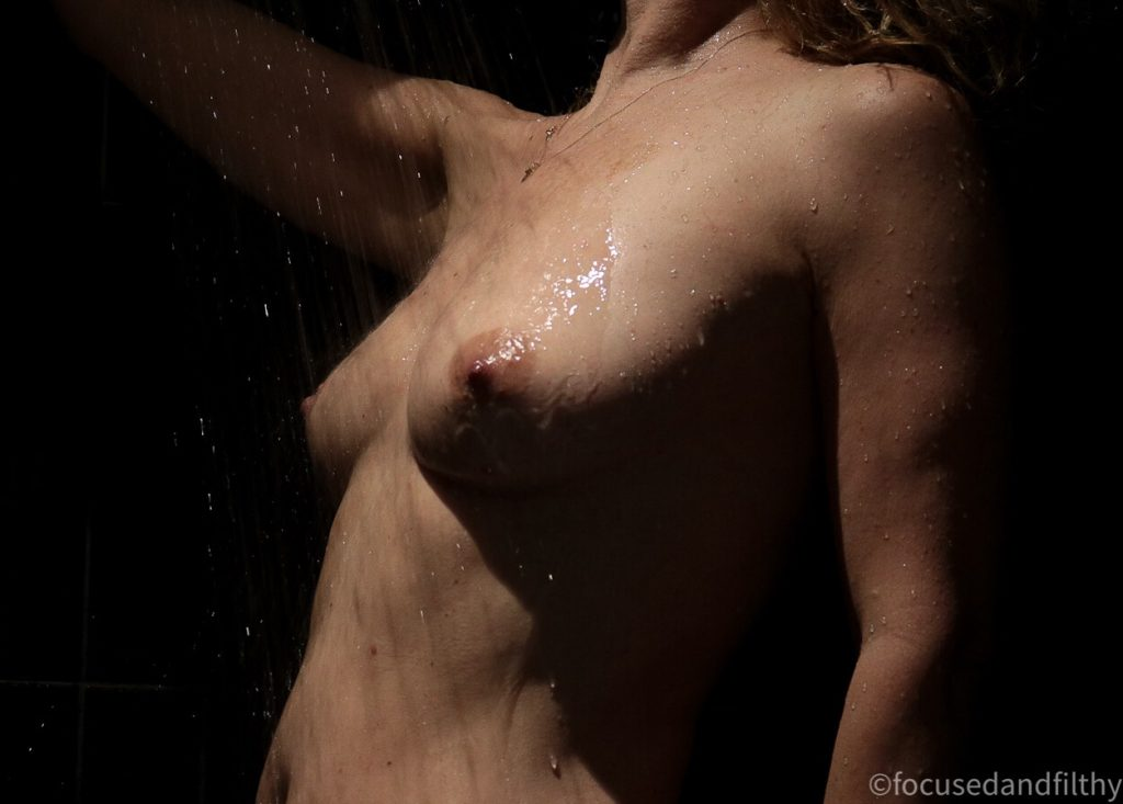 Colour photograph close up of a woman in the shower  showing her from waist to shoulder side on and the water hitting her chest