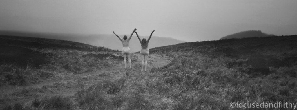 Black and white   Photograph of two naked women walking in the wild Yorkshire moors holding hands with our arms up celebrating the wild weather