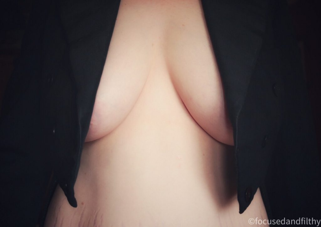 Colour photograph close up of some bare breasts just visible under the black winged lapels of a tailcoat