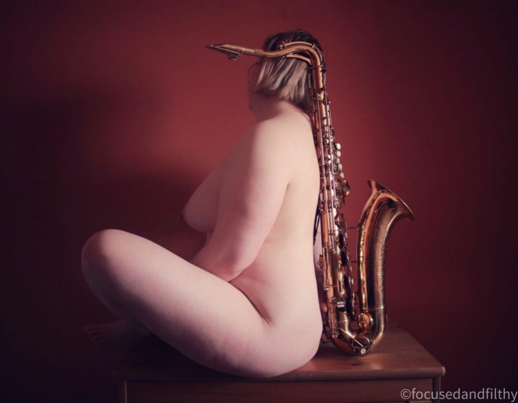 Colour photograph of a naked woman sitting with her back to a tenor saxophone  her shaped reflecting that of the instrument