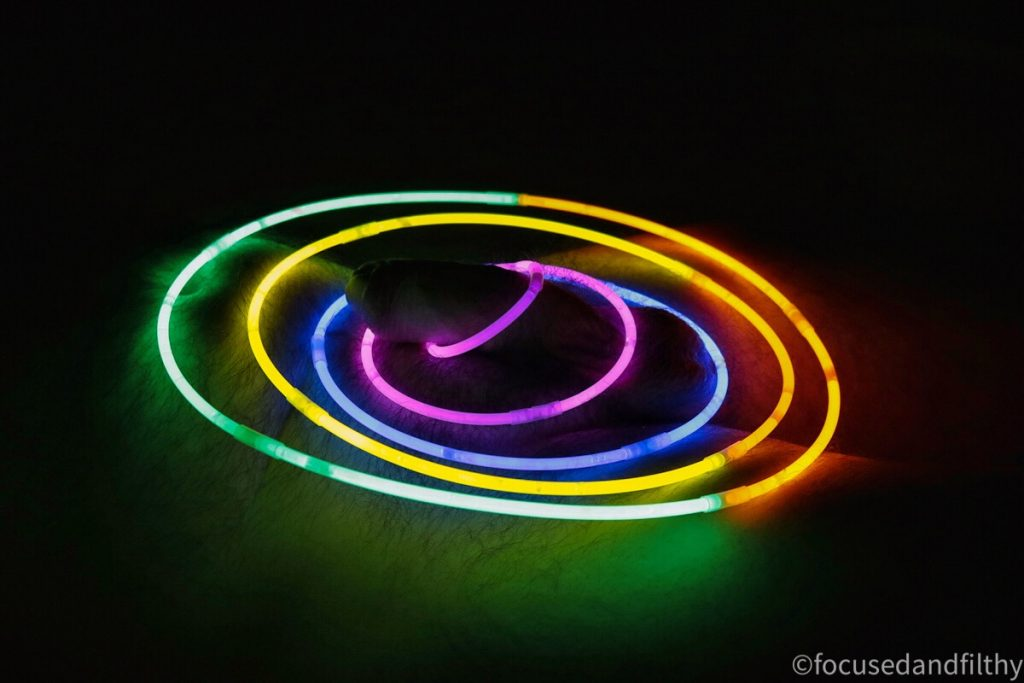 Colour photograph of glow sticks made into increasing in size circles surrounding a soft cock barely lighting up the body