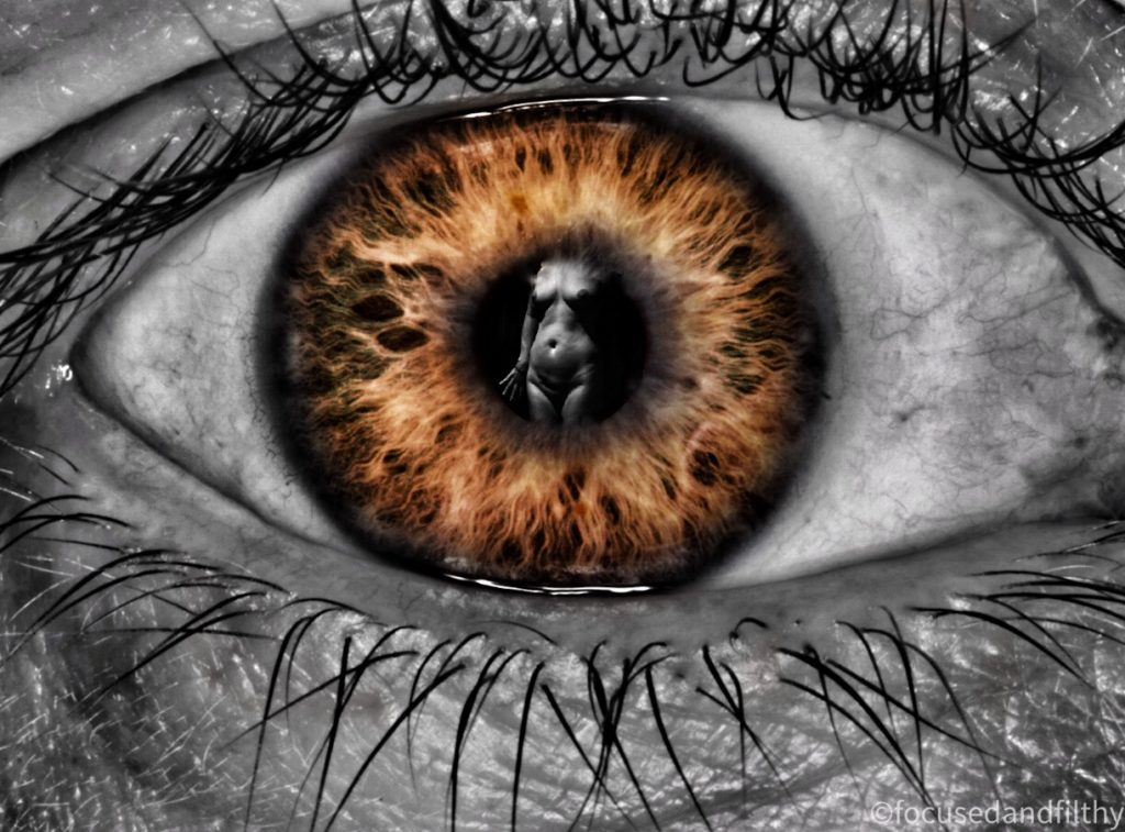 A close up black and white photograph of an eye but the iris is orange and in the pupil there is a black and white image of a naked lady from thighs to neck