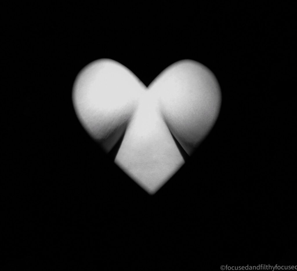 Black and white photograph looking through a heart shape hole at the centre of a naked woman's chest so the cleavage is just  shown  the background is all black but the cleavage it lit so white with shadows shown just under the boobs