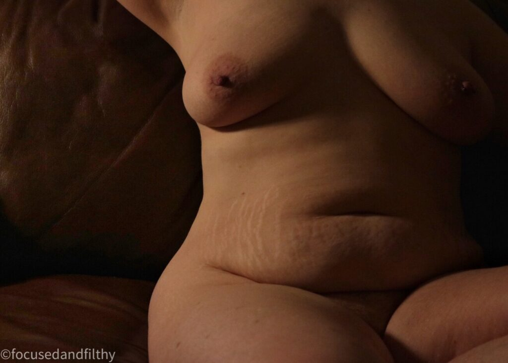 Colour close up photograph of a naked torso of a woman sat on a brown leather sofa showing stretch marks and a soft belly