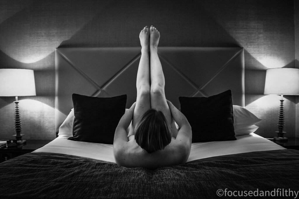 Black and white photograph of naked woman on a bed with her legs straight in the aor dacinf away from you  with cushions and lights either side