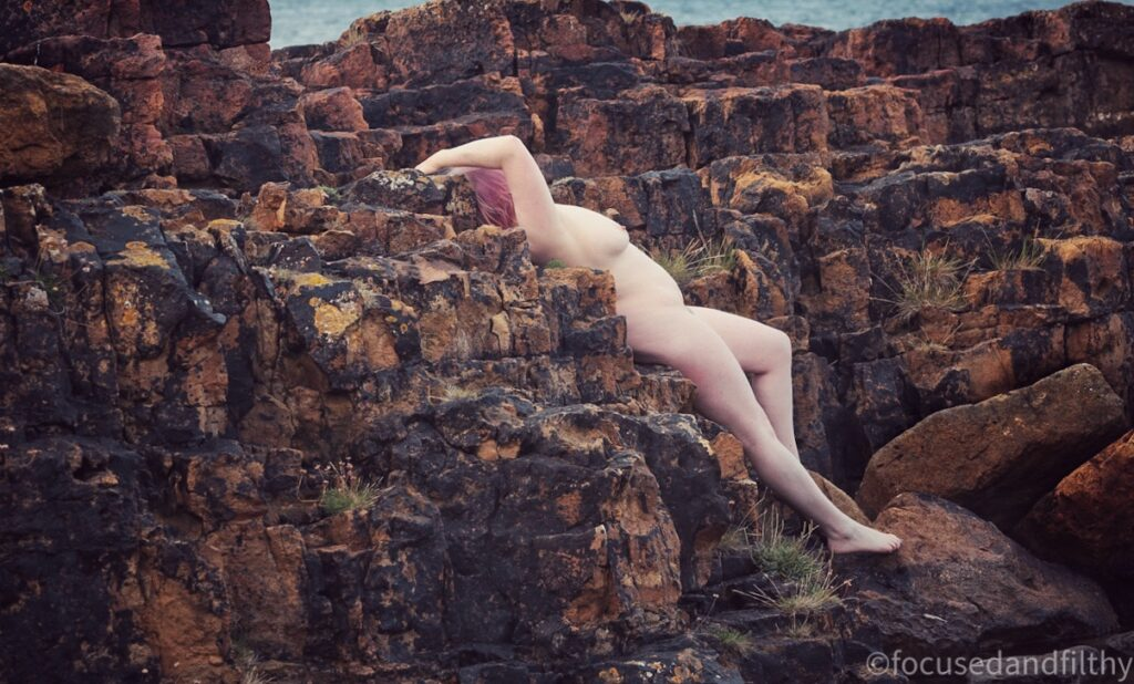 Colour photograph of a pale naked woman lying against geometrically patterned redish rocks by the sea