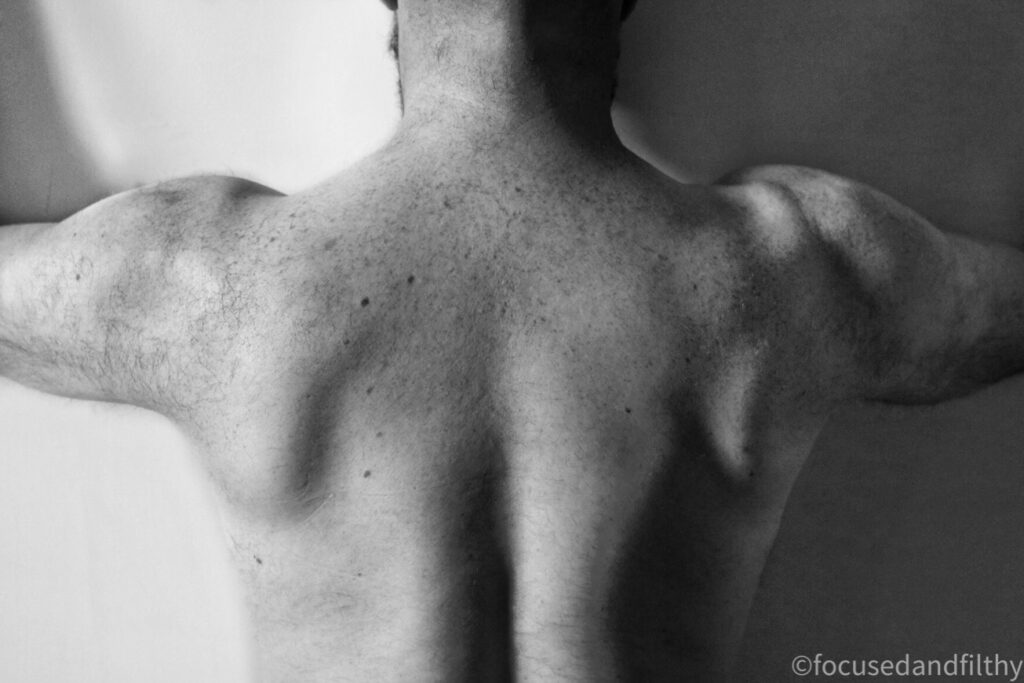 Black and white photograph of a naked man's back with his arms out to his side showing off muscled shoulders and neck